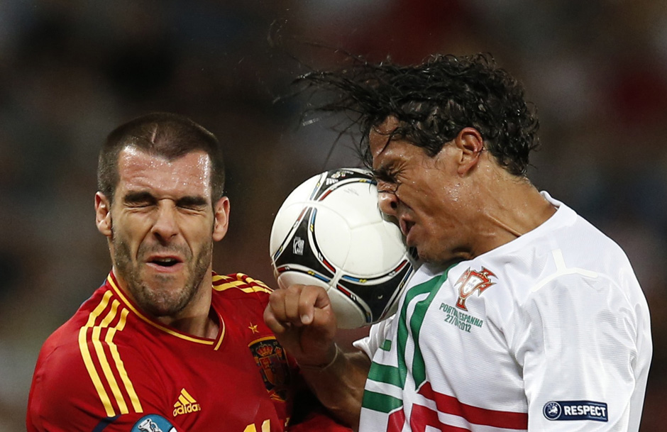 Spain's Negredo and Portugal's Alves jump for header during Euro 2012 semi-final soccer match in Donetsk